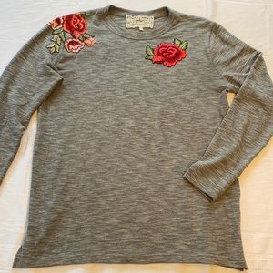 Pink Martini grey sweater with flower embroidered detail on chest and shoulder.